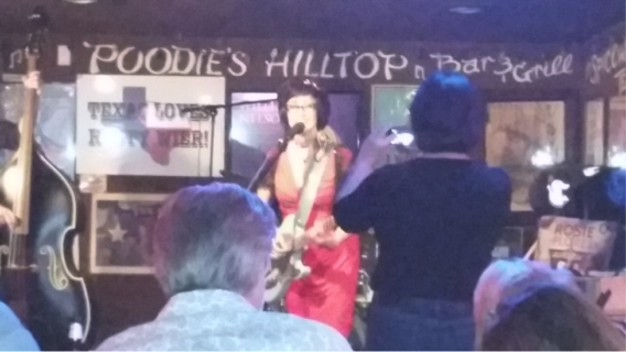 Rosie Flores singing at Poodie's Hilltop Bar & Grill while Kim takes a photo.